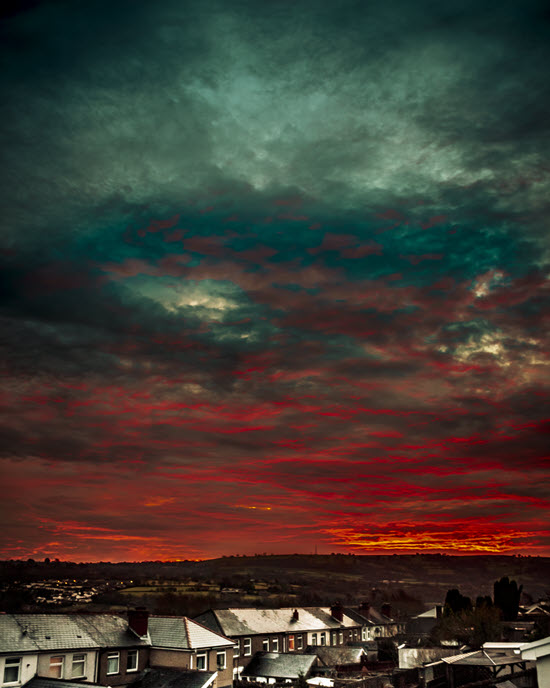 Photo of red and green sky with houses below