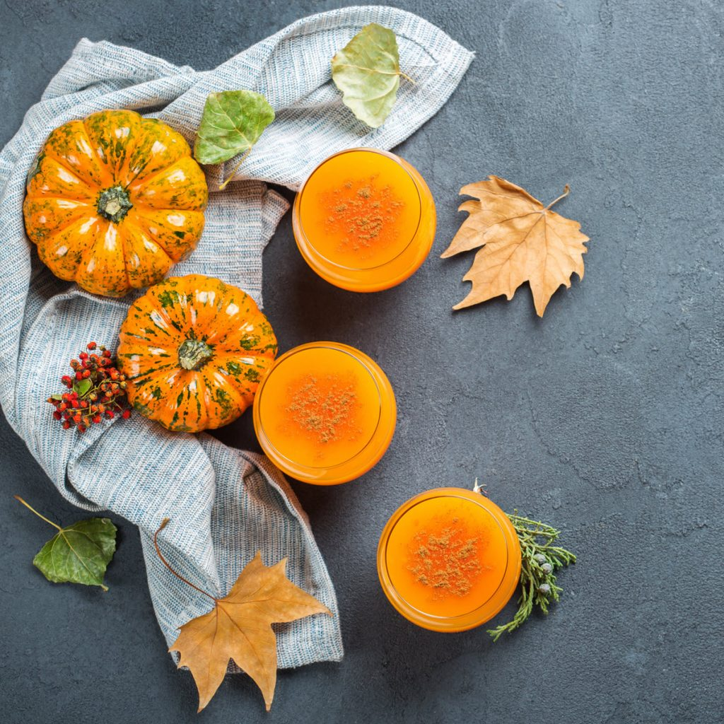 Photo of pumpkins, autumn leaves, and glasses of orange-colored tea - pumpkin spice is nice